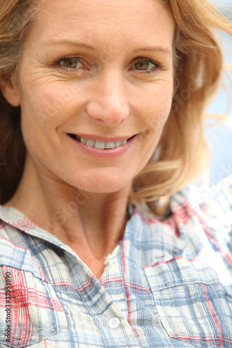 A smiling middle aged woman looking at us.