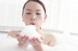 お風呂の泡を手に持つ女性