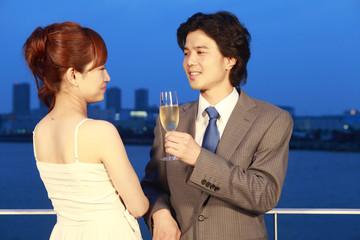 シャンパンを飲みながら会話をしているカップル