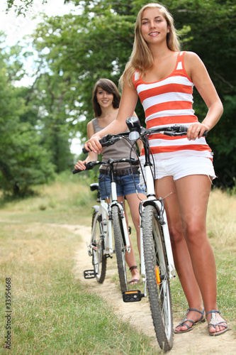 two teenage girls riding bikes in the park