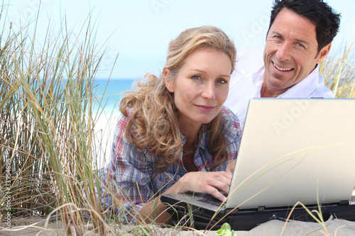 Wife working on laptop on the beach.