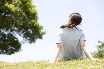 丘に座る女性の後姿