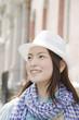 帽子を被って街中を歩く女性