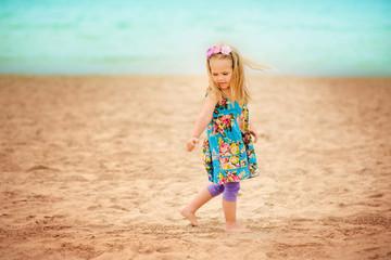 pretty little girl have a fun on sandy beach background