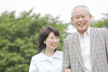 腕を組みながら公園を散歩する老夫婦
