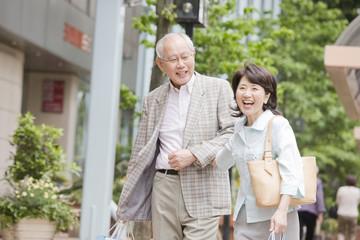 街中を腕を組みながら歩く老夫婦