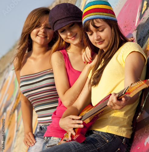 Three beautiful girls with guitar and graffiti wall at backgroun