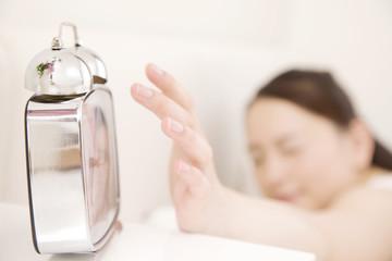 目覚し時計を止める女性