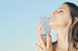 beautiful hot young woman holding glass with ice on her face