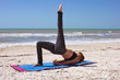woman doing yoga exercise one leg bridge pose on beach