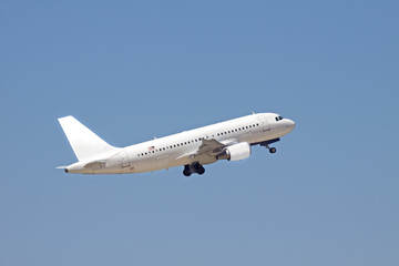 A white passenger plane flies into a blue sky.