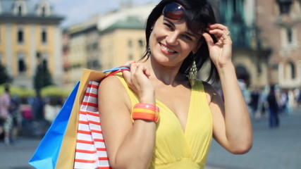 Attractive happy woman with shopping bags in the crowded city