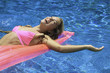 young woman in pink bikini playing in a pool on a pink float