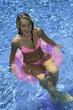 teenage girl in pink bikini playing in a pool on a pink tube
