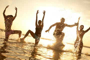 young people dancing and spraying at the beach