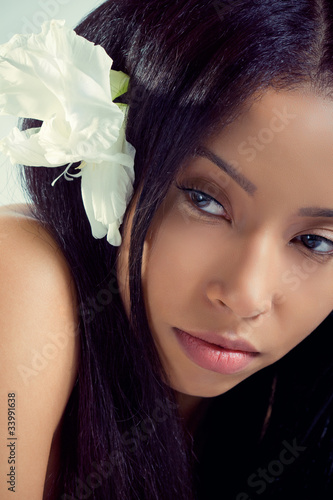 Beautiful young woman with a tropical flower in her hair