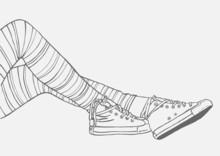 weibliche Beine in gestreiften Strümpfen und Turnschuhen