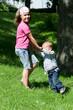 Kinder im Park an den Händen haltend