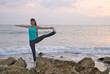 woman doing yoga exercise extended standing hand to toe pose