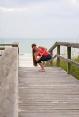 smiling woman doing yoga exercise rotated awkward chair pose