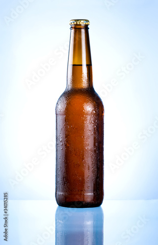 Full brown bottle with condensation on a blue background