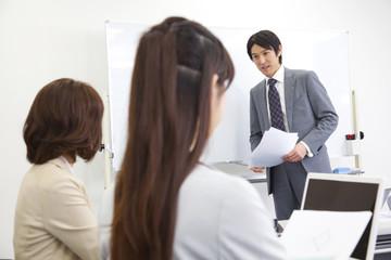 会議室で打合せをするビジネスマンとOL