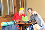 Tramping young couple relax looking in book poster