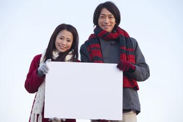 メッセージボードを持つカップル