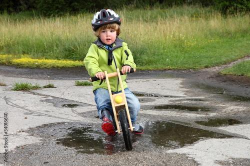 Kind fährt mit Laufrad durch Pfütze