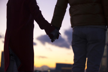 手をつないだカップルの後ろ姿