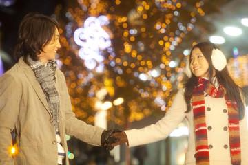 クリスマスイルミネーションに彩られた街を歩くカップル
