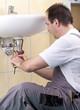 Klemptner repariert ein verstopftes Abflußrohr im Badezimmer.