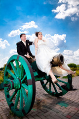 Newly married couple sitting on big cannon and playing in war