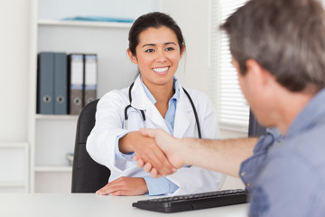 Pretty female doctor shaking a patient's hands