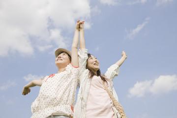手を繋いで両手を伸ばす2人の女性