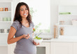 Attractive pregnant woman holding a bowl of salad while standing