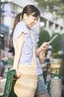 ベンチに寄りかかり携帯電話のメールを確認する女性