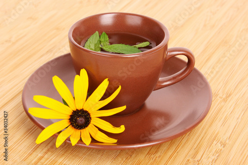 Cup of green tea on the saucer with yellow flower