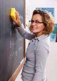 Teacher erasing chalkboard with sponge