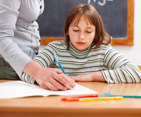 Teacher showing writing to schoolgirl