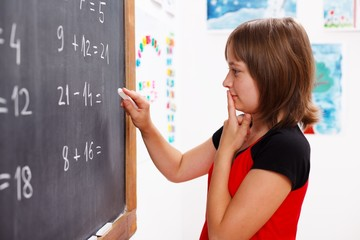 Girl standing in front of chalkboard and thinking
