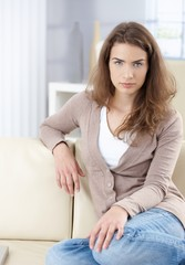 Beautiful woman sitting on sofa at home