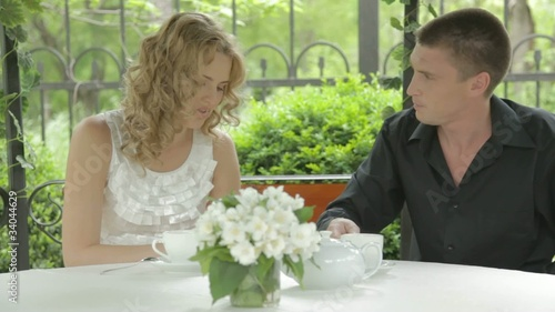 Beautiful young couple drinking tea in summer cafe and talking
