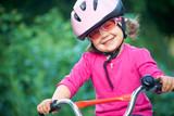 Adorable girl in pink safety helmet