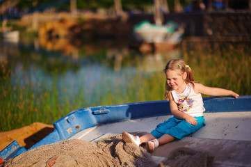 happy girl sit on a boat on coast lake background
