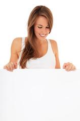 Attraktive junge Frau schaut weißes Schild hinab