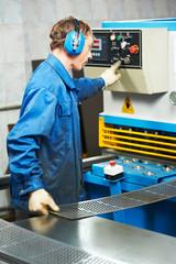 worker operating guillotine shears machine