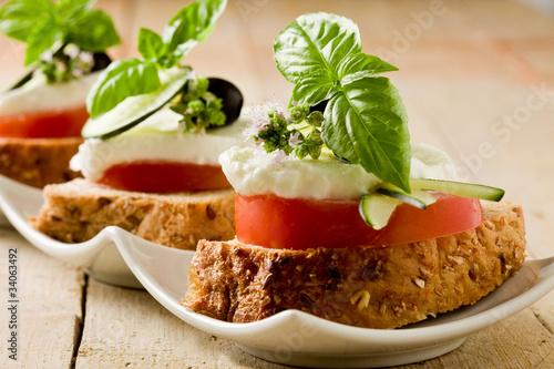 Tartine di pomodoro e mozzarella su letto di pane ai cereali