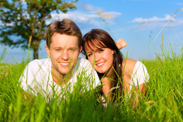 Happy couple lying on a meadow
