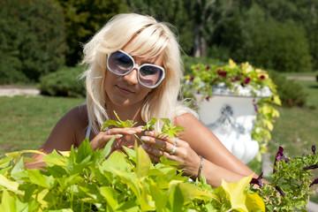 Блондинка разглядывает листья цветов.